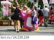 """Купить «Люди и скульптура бело-розового пингвина на праздничной площадке на Манежной площади. Фестиваль «Московское мороженое» из цикла """"Московские сезоны""""», эксклюзивное фото № 24239239, снято 2 июля 2016 г. (c) lana1501 / Фотобанк Лори"""