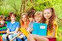 Group of happy kids sitting with books in the park, фото № 24241771, снято 9 мая 2016 г. (c) Сергей Новиков / Фотобанк Лори