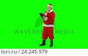 Купить «Santa claus using digital tablet», видеоролик № 24245979, снято 15 сентября 2019 г. (c) Wavebreak Media / Фотобанк Лори