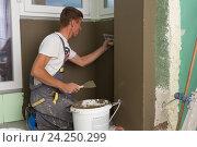 Купить «Штукатур за работой, ремонт квартиры. Финишная отделка», фото № 24250299, снято 22 мая 2019 г. (c) Matej Kastelic / Фотобанк Лори