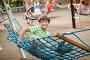 Веселый мальчик качается в гамаке на детской площадке, фото № 24258863, снято 30 июля 2016 г. (c) Юлия Кузнецова / Фотобанк Лори