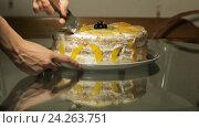 Девушка с ножом разрезает торт со взбитыми сливками на стеклянном столе. Стоковое видео, видеограф Video Kot / Фотобанк Лори