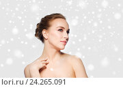 Купить «beautiful young woman touching her neck over snow», фото № 24265091, снято 14 апреля 2016 г. (c) Syda Productions / Фотобанк Лори