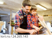 Купить «father and son with ax and wood plank at workshop», фото № 24265143, снято 14 мая 2016 г. (c) Syda Productions / Фотобанк Лори