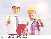 Купить «smiling builders in hardhats with tablet pc», фото № 24265327, снято 21 сентября 2014 г. (c) Syda Productions / Фотобанк Лори