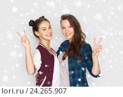 Купить «happy teenage girls hugging and showing peace sign», фото № 24265907, снято 19 декабря 2015 г. (c) Syda Productions / Фотобанк Лори