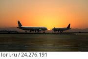 Купить «Два самолета на фоне закатного солнца в аэропорту Аттика (Греция, апрель 2015 года)», фото № 24276191, снято 2 июля 2020 г. (c) oleg savichev / Фотобанк Лори