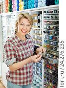 Купить «Mature glad woman customer picking various buttons», фото № 24276235, снято 23 мая 2019 г. (c) Яков Филимонов / Фотобанк Лори