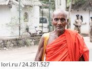 Портрет пожилого ланкийского буддистского монаха на фоне велосипеда машины и полицейского, фото № 24281527, снято 3 ноября 2009 г. (c) Эдуард Паравян / Фотобанк Лори