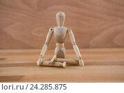 Купить «Wooden figurine sitting in a lotus position», фото № 24285875, снято 23 августа 2016 г. (c) Wavebreak Media / Фотобанк Лори