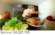 Купить «Мужчина открывает холодильник, смотрит на овощи и откусывает от сосиски», видеоролик № 24287103, снято 10 апреля 2016 г. (c) Андрей Шалари / Фотобанк Лори