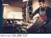 Professional car mechanic balancing car wheel on balancer in au. Стоковое фото, фотограф Andrejs Pidjass / Фотобанк Лори