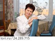 Купить «Приятная пожилая женщина в белой блузке сидит, облокотившись на спинку стула, у себя дома», фото № 24289715, снято 29 ноября 2016 г. (c) Лариса Капусткина / Фотобанк Лори