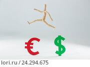 Купить «Wooden figurine jumping over dollar and euro symbol», фото № 24294675, снято 23 августа 2016 г. (c) Wavebreak Media / Фотобанк Лори