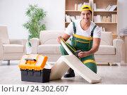 Купить «Furniture repairman repairing armchair at home», фото № 24302607, снято 27 октября 2016 г. (c) Elnur / Фотобанк Лори