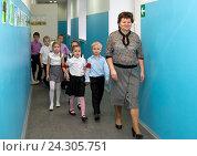Купить «Учитель ведет детей из класса по школьному коридору», эксклюзивное фото № 24305751, снято 23 октября 2015 г. (c) Вячеслав Палес / Фотобанк Лори