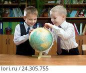 Купить «Два школьника рассматривают глобус», эксклюзивное фото № 24305755, снято 3 ноября 2015 г. (c) Вячеслав Палес / Фотобанк Лори