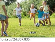 Купить «Group of active kids playing football together on green lawn in park», фото № 24307835, снято 7 июля 2020 г. (c) Яков Филимонов / Фотобанк Лори
