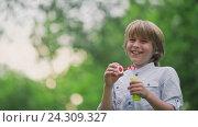 Купить «Smiling boy with a soap bubbles in summer park», видеоролик № 24309327, снято 9 декабря 2019 г. (c) Raev Denis / Фотобанк Лори