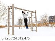 Купить «young man exercising on horizontal bar in winter», фото № 24312475, снято 10 ноября 2016 г. (c) Syda Productions / Фотобанк Лори