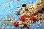 Мюсли с ягодами на деревянном синем фоне, фото № 24312603, снято 27 сентября 2016 г. (c) Афанасьева Ольга / Фотобанк Лори