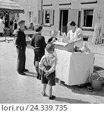 Купить «Kinder kaufen am Eisstand bei der Eisverkäuferin ein Eis, Deutschland 1930er Jahre. Children buying an icecream at an icecream booth, Germany 1930s.», фото № 24339735, снято 23 июля 2018 г. (c) mauritius images / Фотобанк Лори