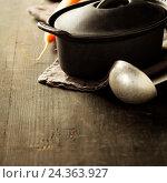 Купить «Чугунная кастрюля и половник на деревянном столе», фото № 24363927, снято 20 октября 2016 г. (c) Наталия Кленова / Фотобанк Лори