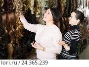 Купить «Two customers purchasing hair extension», фото № 24365239, снято 17 октября 2018 г. (c) Яков Филимонов / Фотобанк Лори