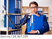 Купить «Handsome businessman chained to the office shelf», фото № 24367335, снято 19 октября 2016 г. (c) Elnur / Фотобанк Лори