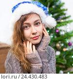 Купить «Портрет молодой красивой девушки в новогоднем колпаке на фоне украшенной елки», фото № 24430483, снято 28 декабря 2014 г. (c) Кекяляйнен Андрей / Фотобанк Лори