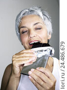 Купить «Senior, chocolate blackboard, bites off,  pleasure-fully, portrait  Series, women portrait, seniors, woman, well Age, well Ager, 60-70 years, happily,...», фото № 24486679, снято 28 мая 2018 г. (c) mauritius images / Фотобанк Лори