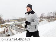 Купить «man in earphones running along winter bridge», фото № 24492459, снято 10 ноября 2016 г. (c) Syda Productions / Фотобанк Лори
