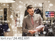 Купить «happy young man choosing shirt in clothing store», фото № 24492691, снято 1 апреля 2016 г. (c) Syda Productions / Фотобанк Лори