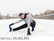 Купить «man exercising and stretching leg on winter bridge», фото № 24492855, снято 10 ноября 2016 г. (c) Syda Productions / Фотобанк Лори