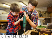Купить «father and son with drill working at workshop», фото № 24493139, снято 14 мая 2016 г. (c) Syda Productions / Фотобанк Лори