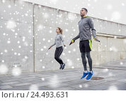 Купить «man and woman exercising with jump-rope outdoors», фото № 24493631, снято 17 октября 2015 г. (c) Syda Productions / Фотобанк Лори