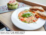 Купить «plate of delicious gazpacho soup at restaurant», фото № 24493827, снято 22 сентября 2016 г. (c) Syda Productions / Фотобанк Лори