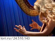 Купить «Красивая девушка играет на арфе в концертном зале во время концерта классической музыки», фото № 24510143, снято 9 декабря 2016 г. (c) Николай Винокуров / Фотобанк Лори