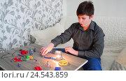 Купить «Teen Boy assembles the electricity from constructor», видеоролик № 24543859, снято 10 декабря 2016 г. (c) Володина Ольга / Фотобанк Лори