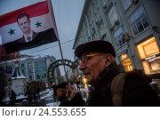 Купить «Мужчина держит флаг Сирии с портретом президента Башара Асада на митинге-шествии коммунистов в городе Москве, Россия», фото № 24553655, снято 7 ноября 2016 г. (c) Николай Винокуров / Фотобанк Лори