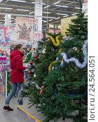 Женщина выбирает новогоднюю елку в супермаркете (2016 год). Редакционное фото, фотограф Юлия Юриева / Фотобанк Лори