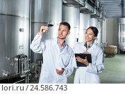 Купить «Man and woman employees on winery manufactory», фото № 24586743, снято 28 мая 2018 г. (c) Яков Филимонов / Фотобанк Лори