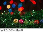 Разноцветные блестящие ёлочные шарики на зелёной мишуре. Стоковое фото, фотограф Глыцко Андрей / Фотобанк Лори