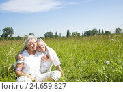 Купить «Senior couple sits happy on a meadow,», фото № 24659827, снято 19 марта 2019 г. (c) mauritius images / Фотобанк Лори