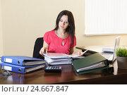 Купить «Молодая женщина работает с документами за столом в офисе», фото № 24667847, снято 6 мая 2016 г. (c) Наталья Гармашева / Фотобанк Лори