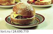 Купить «Cooking hamburger. Three cooked burgers on the small colored plates. HD», видеоролик № 24690719, снято 12 декабря 2016 г. (c) ActionStore / Фотобанк Лори