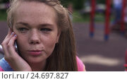 Young attractive girl with freckles speak to phone on playground. Summer park. Стоковое видео, видеограф Александр Багно / Фотобанк Лори