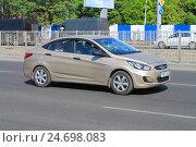 Купить «Автомобиль седан Hyundai Solaris цвета бежевый металлик на дороге в солнечный день», фото № 24698083, снято 11 мая 2016 г. (c) Михаил Рудницкий / Фотобанк Лори