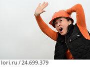 Женщина в каске кричит и прикрывается от опасности сверху. Стоковое фото, фотограф VIACHESLAV KRYLOV / Фотобанк Лори