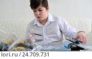Купить «Teen boy collects constructor in room», видеоролик № 24709731, снято 18 декабря 2016 г. (c) Володина Ольга / Фотобанк Лори